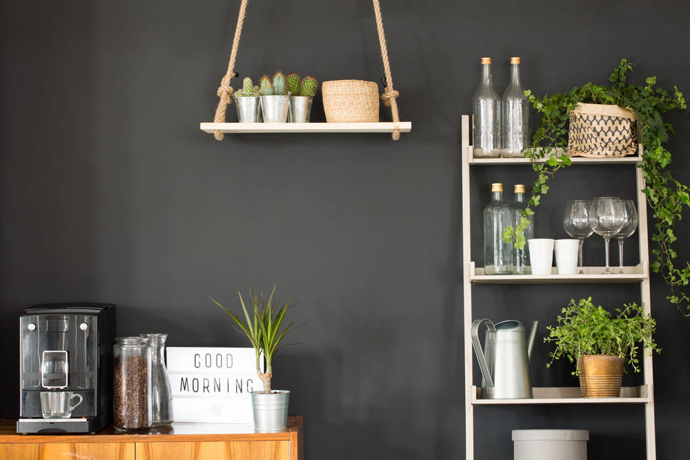 Modern kitchen with black wall, swing shelf and ladder bookcase
